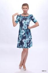В этом платье из трикотажной вискозы основной акцент сделан на горловине, оформленной сложной драпировкой по плечам и собранной в центре на планку. Полуприлегающий силуэт подчеркивает женственные изгибы фигуры, вместе с тем скрывая ее мелкие недостатки за счет рисунка ткани. Такое платье - незаменимая часть летнего офисного гардероба